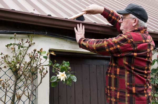 A picture of a man cleaning his eavestroughs.